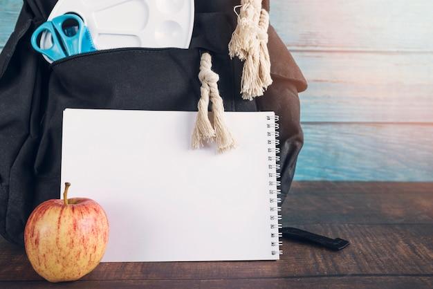 Rugzak met de schaarnotitieboekje en appel van de palletheerser