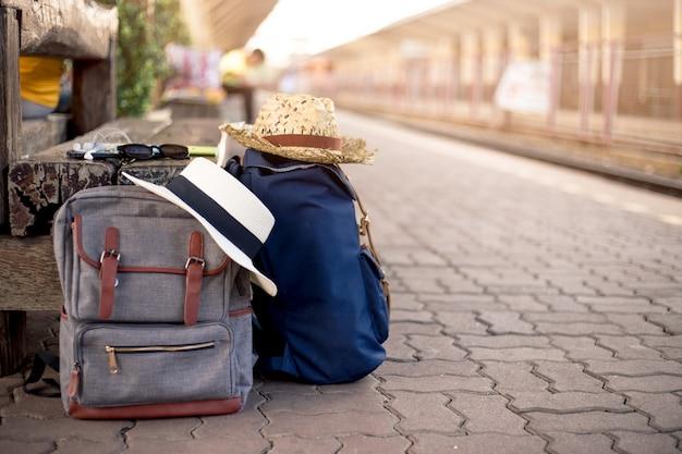 Rugzak met hoed, kaart, zonnebril, oortelefoon en smartphone in treinstation