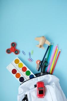 Rugzak met verschillende kleurrijke kantoorbehoeften op lijst.