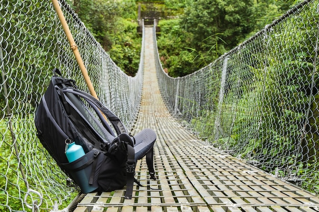 Rugzak met waterfles en bamboestok op voetgangershangbrug. bergwandelen, trekkingconcept. stock foto