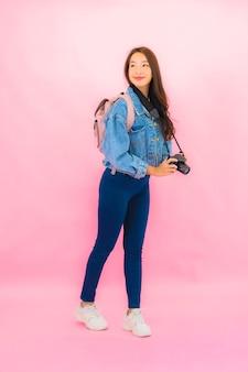 Rugzak of bagage van de portret de mooie jonge aziatische vrouw met camera klaar voor reis in vakantie op roze muur
