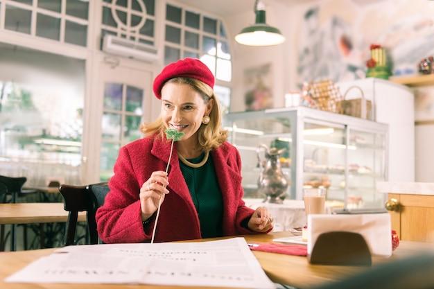 Ruikende bloem. blond-haired volwassen elegante vrouw die rode baret draagt die aardige bloem ruikt