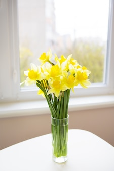 Ruikertje van heldere gele gele narcissen op witte houten lijst.