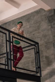 Ruim appartement. groenharige vrouw staat in haar ruime appartement en drinkt 's ochtends koffie