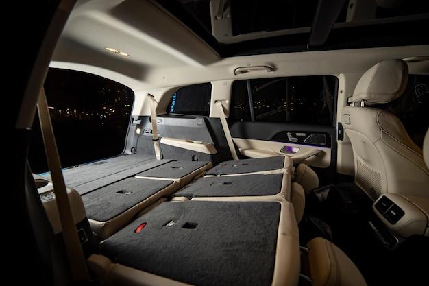 Ruim leeg interieur van premium suv. achterbank neergeklapt in platte flor in luxe dure suv-auto. zijaanzicht van platte flor kofferbak
