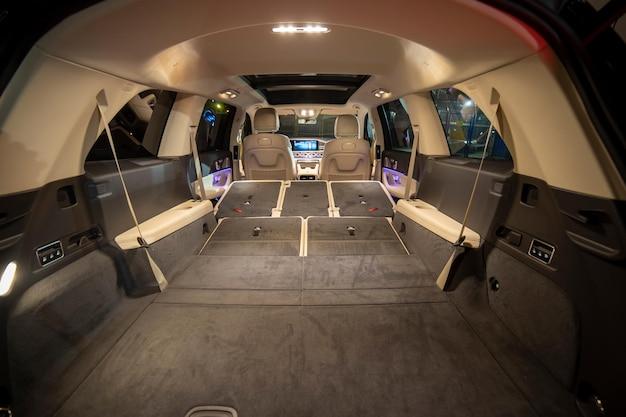 Ruim leeg interieur van premium suv-achterstoelen gevouwen in platte flor in luxe dure suv-auto