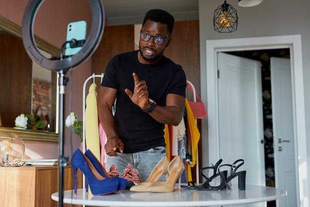 Ruimdenkende afro blogger praat voor de camera, laat nieuwe kleding en schoenen zien