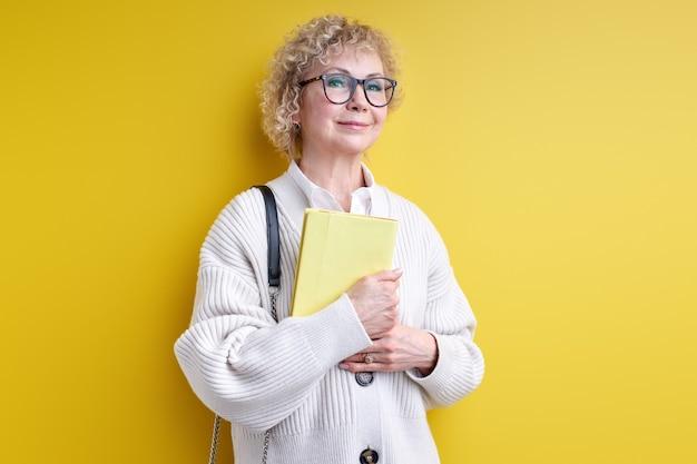 Ruimdenkende senior vrouw met boek in handen, bril dragen, zelfverzekerde leraar klaar om je te onderwijzen, ervaren leraar poseren geïsoleerd op geel