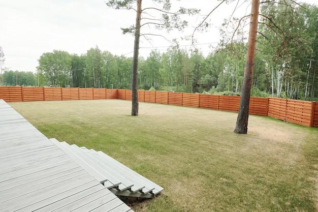 Ruime achtertuin met twee lange bomen omsloten met houten schutting op het platteland