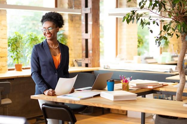 Ruime coworking. binnenhuisarchitect die oranje blouse draagt die in ruime prettige coworking werkt
