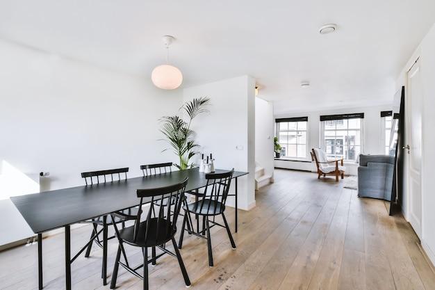 Ruime eetkamer in minimalistische stijl met tafel en stoelen in modern appartement met witte muren en houten vloer