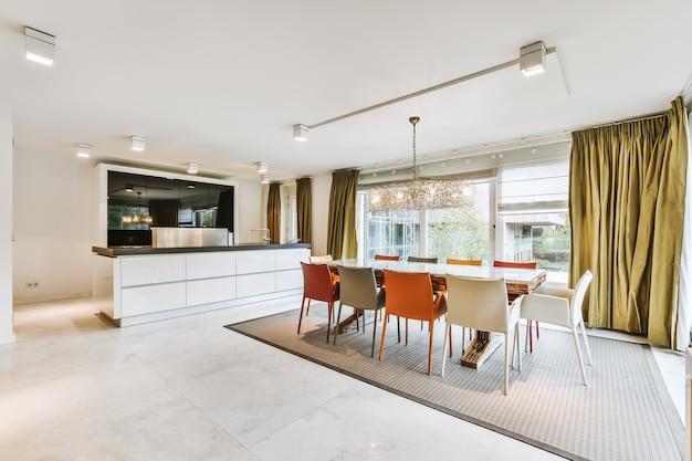Ruime kamer met open minimalistische keuken en grote eettafel met kleurrijke stoelen onder kroonluchter