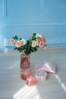 Ruime kamer met zonlicht, bloemen in vaas, kussen, hartvormige doos en cocktails