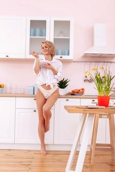 Ruime keuken. jonge zakenvrouw die 's ochtends in lichte ruime keuken staat