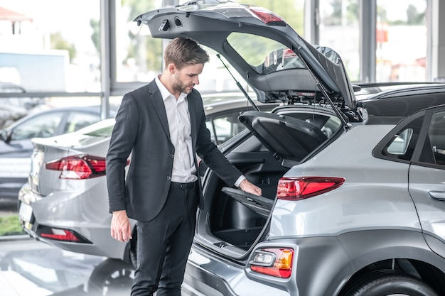Ruime koffer. geconcentreerde geïnteresseerde jonge man in pak kijkend naar ruime open kofferbak van nieuwe auto in showroom