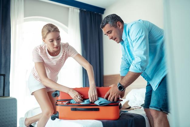 Ruime koffer. geconcentreerde man en vrouw doen hun best om hun koffer vol kleding dicht te doen.