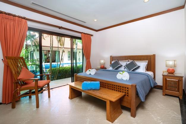 Ruime slaapkamer met blauw laken en houten wadrobe