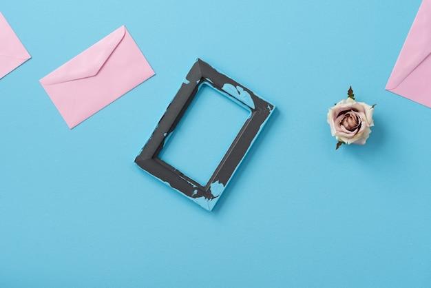 Ruimte fotolijst en roze envelop met roze bloem op blauwe pastel achtergrond
