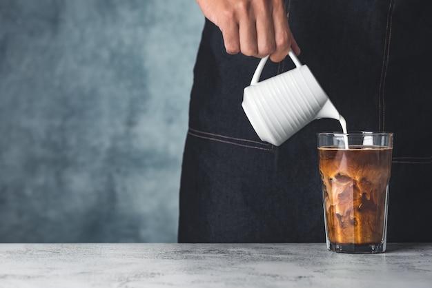 Ruimte ijskoffie met hand giet melk voedsel achtergrond