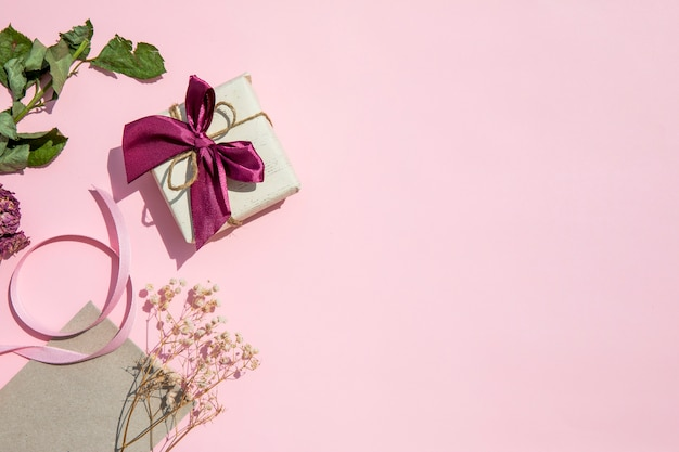 Ruimte roze achtergrond met cadeau kopiëren