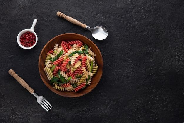 Ruimte veganistische kleur pasta in houten plaat op zwarte kleur achtergrond