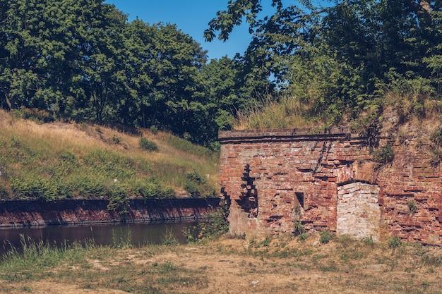 Ruïnes van een gebouw met bakstenen muren. oude verwoeste vesting door het rivierkanaal en bos in de buurt. stock fotografie.