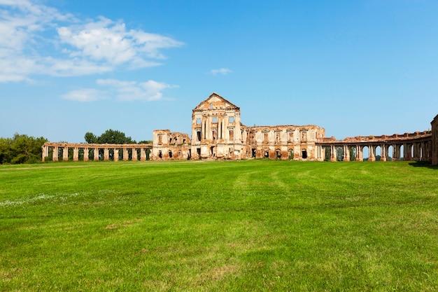 Ruïnes van het beroemde paleis in de stad ruzhany, wit-rusland. constructie van rode baksteen uit klei. voordat het kasteel groen gras en de blauwe lucht erboven groeit