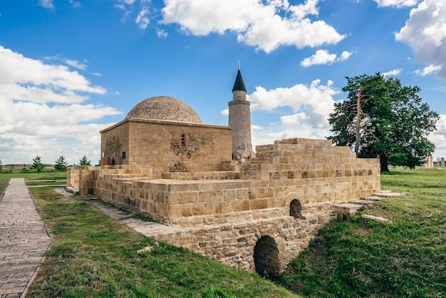 Ruïnes van het graf van de oude khan in het fort van de bolghar-heuvel en de kleine minaret op de achtergrond.