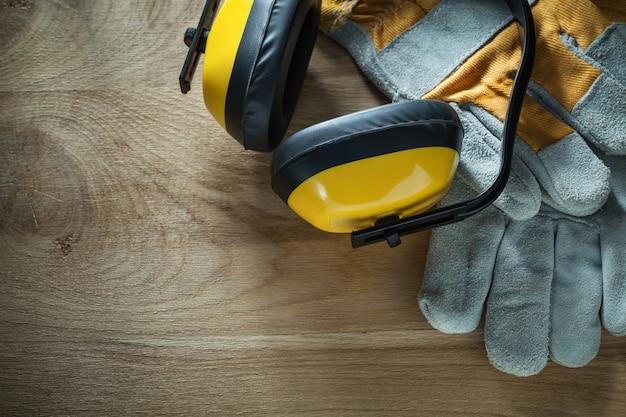 Ruisonderdrukking oorkappen veiligheidshandschoenen op houten bord