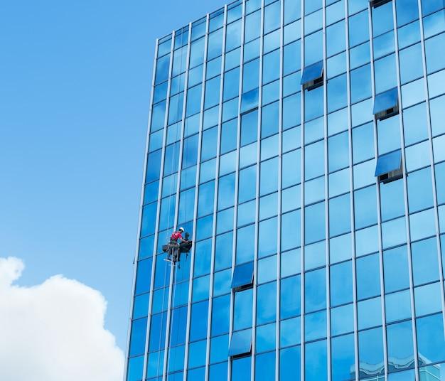 Ruitenreiniger werkt aan een hangende glazen gevel