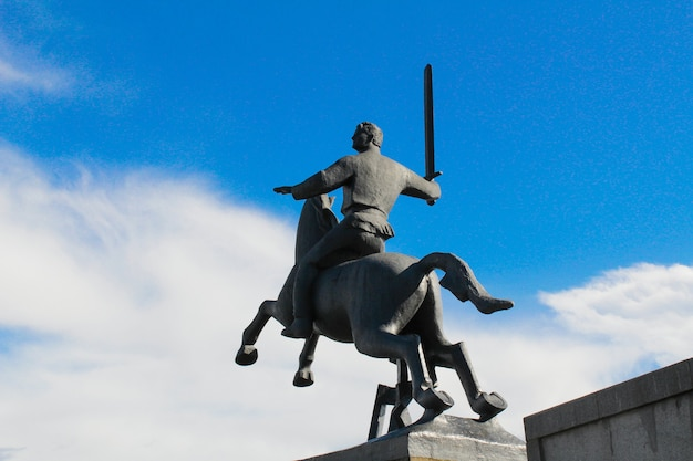 Ruiter met zwaard monument voor de overwinning op de achtergrond van blauwe lucht met witte wolken