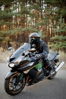 Ruiter op een motor die bij zonsondergang rijdt - ruimte voor uw tekst, fietser en motor klaar om te rijden
