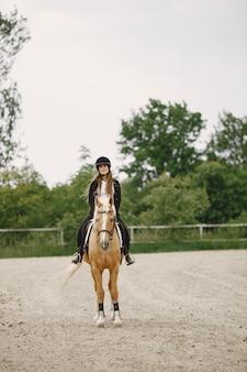 Ruitervrouw die haar paard berijdt op een boerderij. vrouw heeft lang haar en zwarte kleding. vrouwelijke ruiter op haar bruin paard.