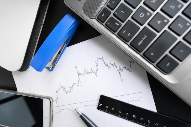 Ruitjespapier, laptop, telefoon en een pen op de kantoortafel