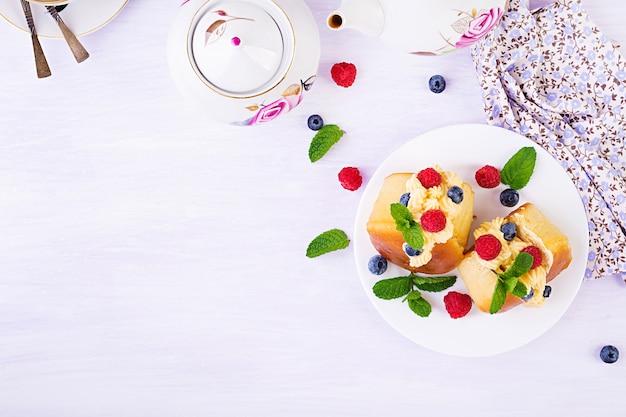 Rum baba versierd met slagroom en verse frambozen, bosbessen. savarin met rum, room en bessen. italiaanse keuken. bovenaanzicht