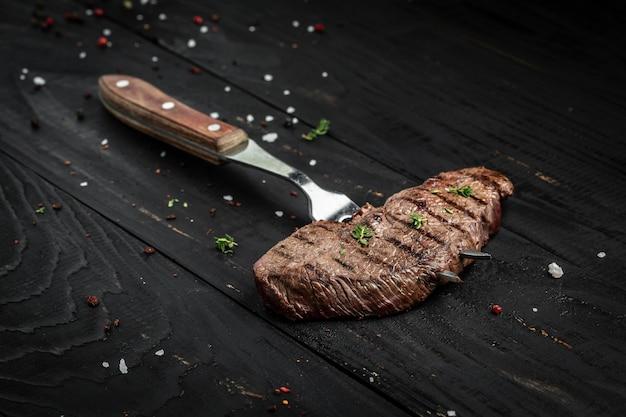 Rump steak op vork op donkere houten achtergrond. banner, menu recept plaats voor tekst, bovenaanzicht.