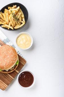 Rundergehakt hamburger en frietjes op witte ondergrond met kopie ruimte.
