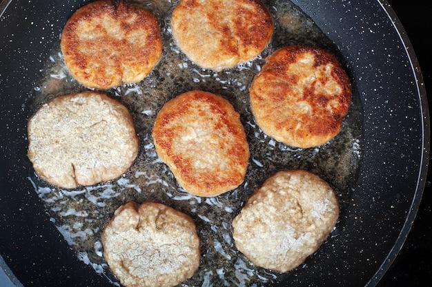 Rundergehaktkoteletten worden gebakken in een pan