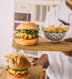 Runderkaasburger met friet op een plank
