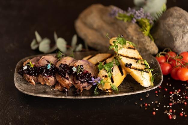 Runderrolletje met bessenjam en gegrilde ciabatta, versierd met verse bloemen en spruitjes van jonge erwten.
