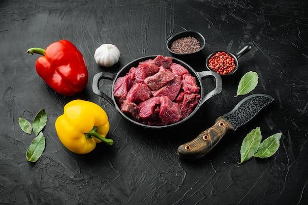 Runderstoof rauwe ingrediënten set met zoete paprika, in gietijzeren koekenpan