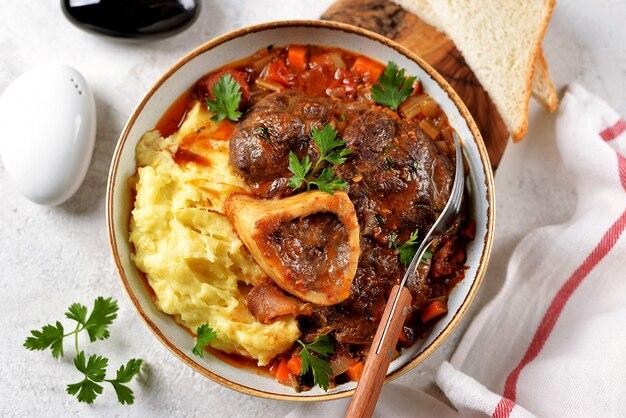 Runderstoofpot met uien, wortelen, selderij, tomaten, tijm met aardappelpuree