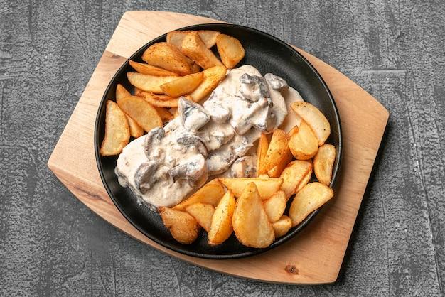 Rundertong in romige champignonsaus. met gebakken aardappelen op een rustieke manier. in een gietijzeren pan met een houten standaard. uitzicht van boven. op een grijze betonnen achtergrond.