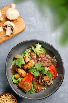 Rundsalade met champignons, pijnboompitten en tomaten. salade met ingrediënten bovenaanzicht.