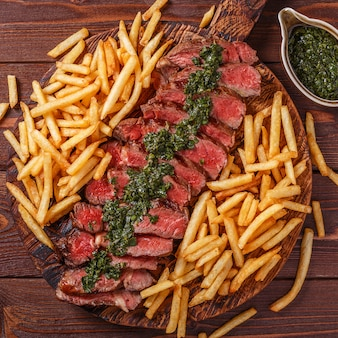 Rundvlees barbecue ribeye steak met chimichurri saus en frietjes.