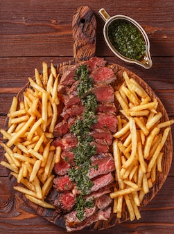 Rundvlees barbecue ribeye steak met chimichurri saus en frietjes.