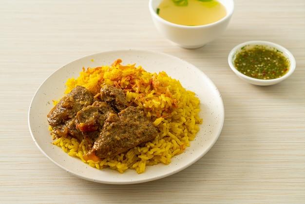 Rundvlees biryani of kerrie rijst en rundvlees - thais-islamitische versie van indiase biryani, met geurige gele rijst en rundvlees - islamitische eetstijl