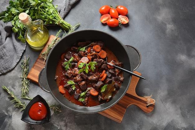 Rundvlees bourguignon in een pan. stoofpotje met rode wijn, wortelen, uien, knoflook, champignons en spek