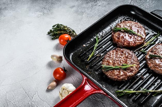 Rundvlees burgerpasteitjes sissend op een hete barbecuepan