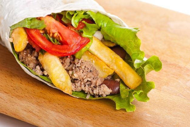 Rundvlees burrito met gele en rode paprika, gebakken aardappel en tomaat op plaat